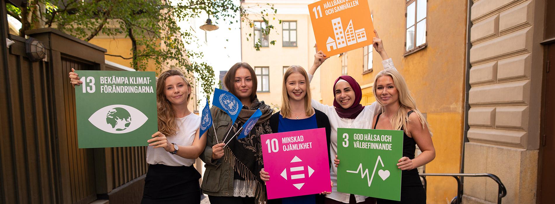 Några av FN-förbundets ambassadörer håller upp skyltar för de globala målen