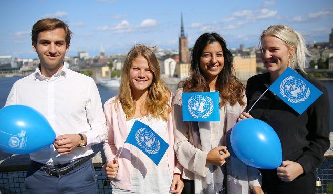 Ambassadörer viftar med FN-flaggor och ballonger