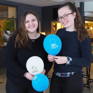 Linnea Lindblom och Stina Lindqvist, sekreterare respektive ordförande i FN-elevföreningen på Högbergsskolan, står med globala-målen och Svenska FN-förbundet-ballonger