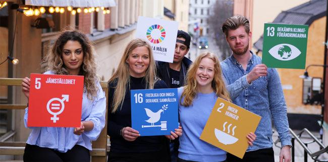ungdomar håller globala målen-skyltar