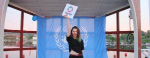 Gld tjej håller upp skylt för de globala målen på ungdomskonferens om FN