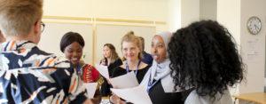 Glada ungdomar löser en uppgift på vår ungdomskonferens om FN
