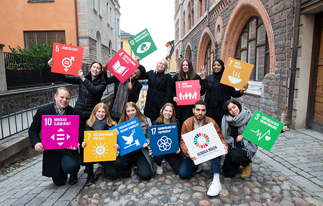 Ambassadörer som håller upp skyltar med de globala målen